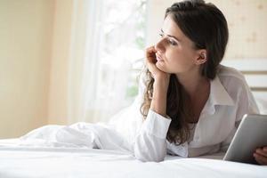 femme heureuse allongée sur le lit avec tablette photo