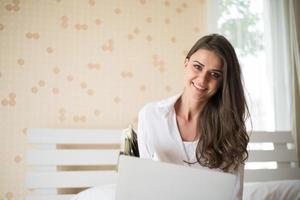 heureuse belle femme travaillant sur un ordinateur portable sur le lit dans la maison photo
