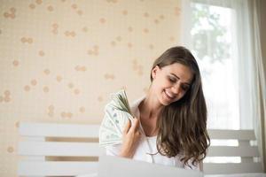 femme avec un billet de banque en dollars sur le lit photo