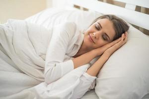 belle jeune femme dormant dans son lit photo