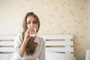 belle femme buvant de l'eau douce dans le lit le matin photo
