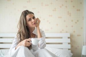 belle femme dans sa chambre buvant du café le matin photo
