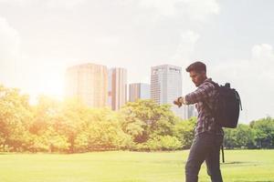 jeune homme hipster regardant sa montre derrière la vue sur la ville depuis le parc. photo