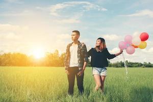 jeune couple courant et tenant un ballon dans l'herbe verte ci-dessous photo