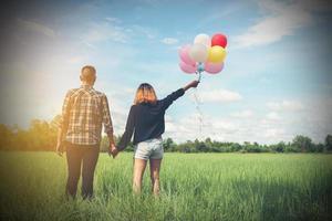 dos d'un jeune couple asiatique heureux tenant un ballon et marchant ensemble. photo