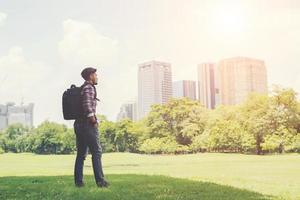 jeune homme hipster profite de la vue sur la ville depuis le parc lors d'un voyage photo