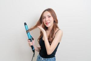Portrait belle femme asiatique à l'aide d'un bigoudi ou d'un fer à friser sur fond blanc photo