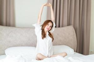 portrait belle femme asiatique se réveiller sur le lit le matin photo