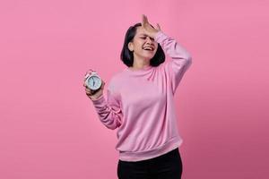 Une jeune femme choquée tient un réveil blanc à la main photo