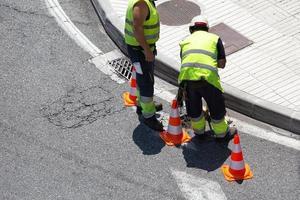 travailleurs réparant une route goudronnée sur la ville photo