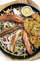 Assiette de repas de saucisses et de pommes de terre biologiques traditionnelles allemandes mixtes comprenant du nurnberger, de l'agneau et du porc avec de la salade et de la moutarde photo
