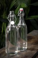 bouteille d'eau à rabat en verre blanc clair à l'extérieur sur une table de jardin photo