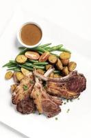 côtelettes d'agneau bio australien avec des légumes et de la sauce sur fond blanc photo