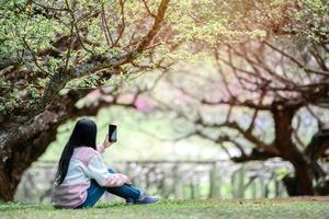 voyageuse asiatique prendre selfie dans le jardin photo