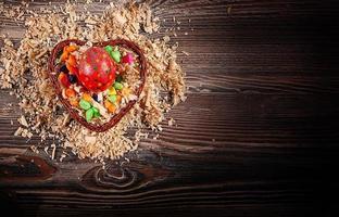 Oeufs de Pâques pascals colorés dans le panier coeur photo