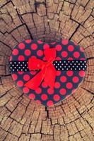 forme de coeur de boîte-cadeau sur tronc de bois photo