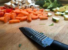 Carotte et champignons hachés au couteau sur la table de la cuisine photo