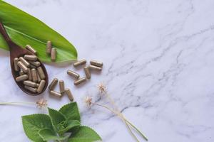 capsule de fines herbes de la nature d'herbe sur le marbre blanc photo