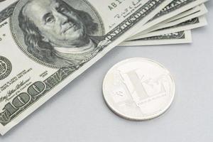 pièce de monnaie litecoin et une pile de billets en dollars américains photo