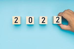 main de l'homme a mis un bloc de bois du nouvel an 2022 sur fond bleu doux photo