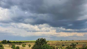 ciel sombre sur un champ jaune. un orage arrive. photo