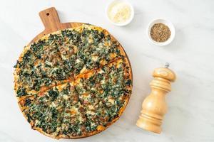pizza aux épinards et au fromage sur plateau en bois - style végétalien et végétarien photo