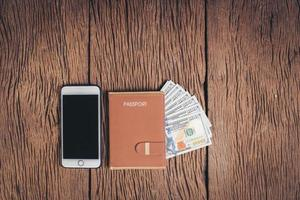 passeport vue de dessus avec de l'argent sur fond de bois, concept de tourisme. photo