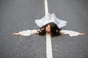 vue de face d'une femme allongée sur une route goudronnée avec ses bras tendus photo
