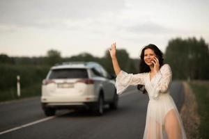 jeune femme parlant au téléphone et saluant pour arrêter une voiture sur la route rurale photo