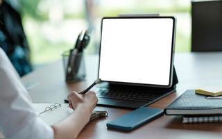 femme d'affaires main travaillant sur un ordinateur et écrivant sur une note photo