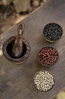 grains de poivre blanc rouge et noir biologique dans un présentoir en bois photo