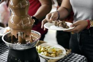 Machine de restauration de fontaine de chocolat avec des brochettes de fruit sur la table rustique de buffet photo