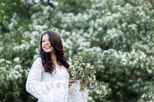 portrait de jeune femme dans le parc dans les branches fleuries photo