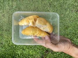 une main tenant des durians à l'intérieur d'un récipient en plastique, prêt à être emporté. photo