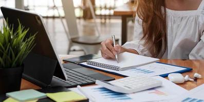une femme asiatique en gros plan prend des notes sur son cahier pour en ligne photo