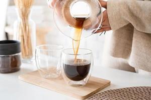 Jeune femme prépare du café dans une cafetière, verse du café dans le verre photo