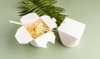 boîte de papier wok ouverte avec des nouilles et des baguettes photo