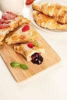 délicieux croissants dorés remplis de confiture de fraises sur planche de bois photo