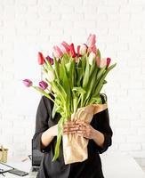 femme d'affaires debout près du bureau avec un bouquet de tulipes fraîches photo