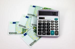 100 billets en euros éparpillés avec calculatrice photo