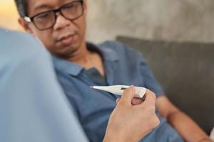 thermostat dans la main du médecin, examen patient de sexe masculin âgé. photo