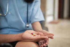 pilules dans la main du patient pendant l'examen d'une femme médecin. photo