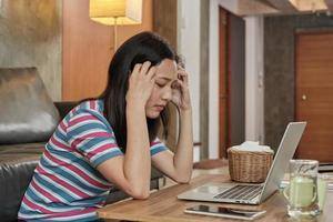 femme asiatique travaillant à la maison est stressée et mal de tête. photo