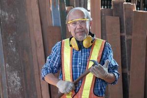 charpentier asiatique âgé masculin dans une usine en bois. photo