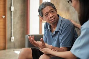 Un médecin thérapeute féminin examine un patient âgé à la maison. photo