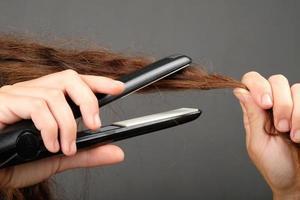 lissage des cheveux bouclés avec un fer à friser, soins capillaires. photo