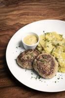 boulettes de viande frikadellen allemandes avec pommes de terre frites crémeuses à l'oignon et sauce moutarde sur fond de table en bois photo