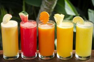 Sélection de verres de jus de fruits biologiques frais mélangés sur une table de jardin ensoleillée photo