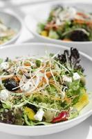 salades biologiques fraîches mélangées dans des bols sur une table de restaurant blanche photo