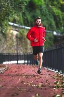 un athlète court sur la piste cyclable à l'automne photo